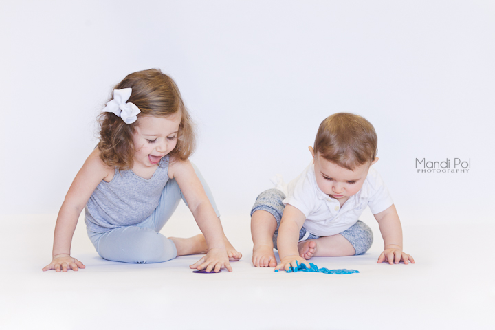 cute brother and sister playing in paint