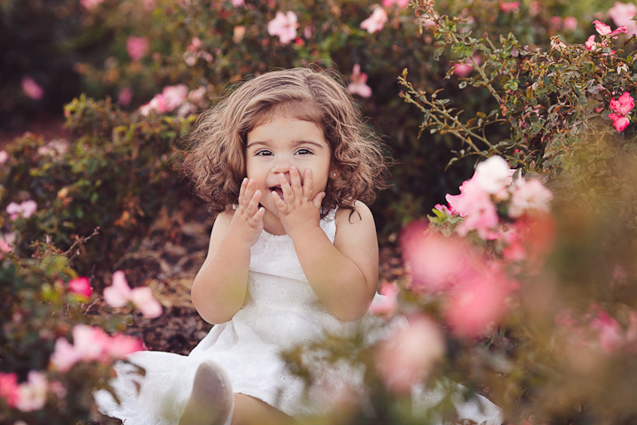 adorable baby girl by pink flowers