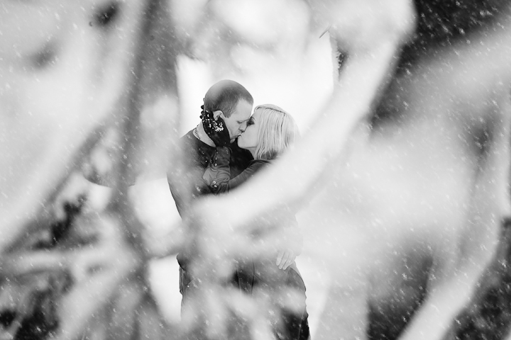 photograph of engaged couple kissing in snow