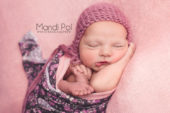 portrait of newborn baby girl on pink blanket
